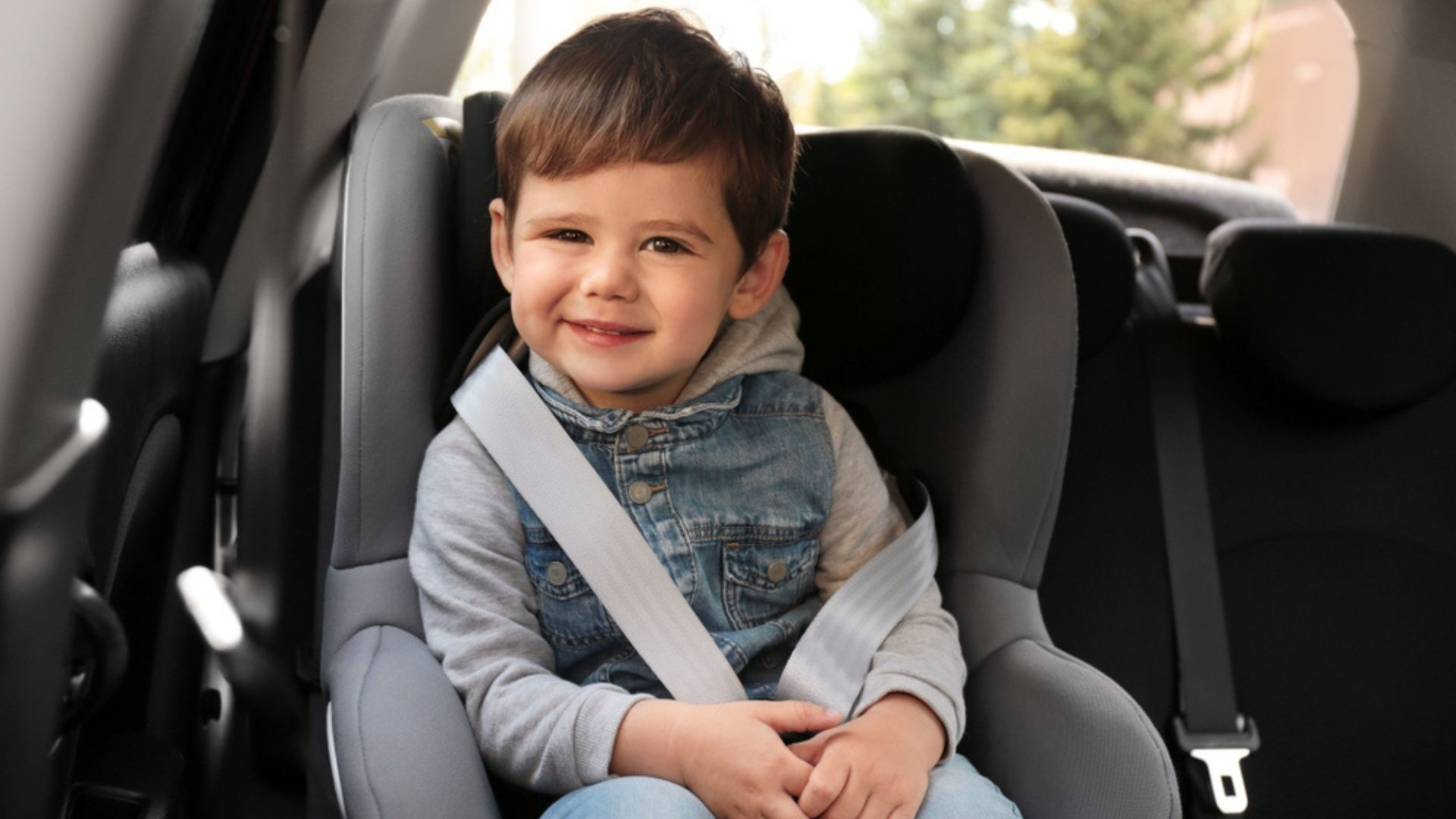 3 year old boy seat in the car seat and smiling